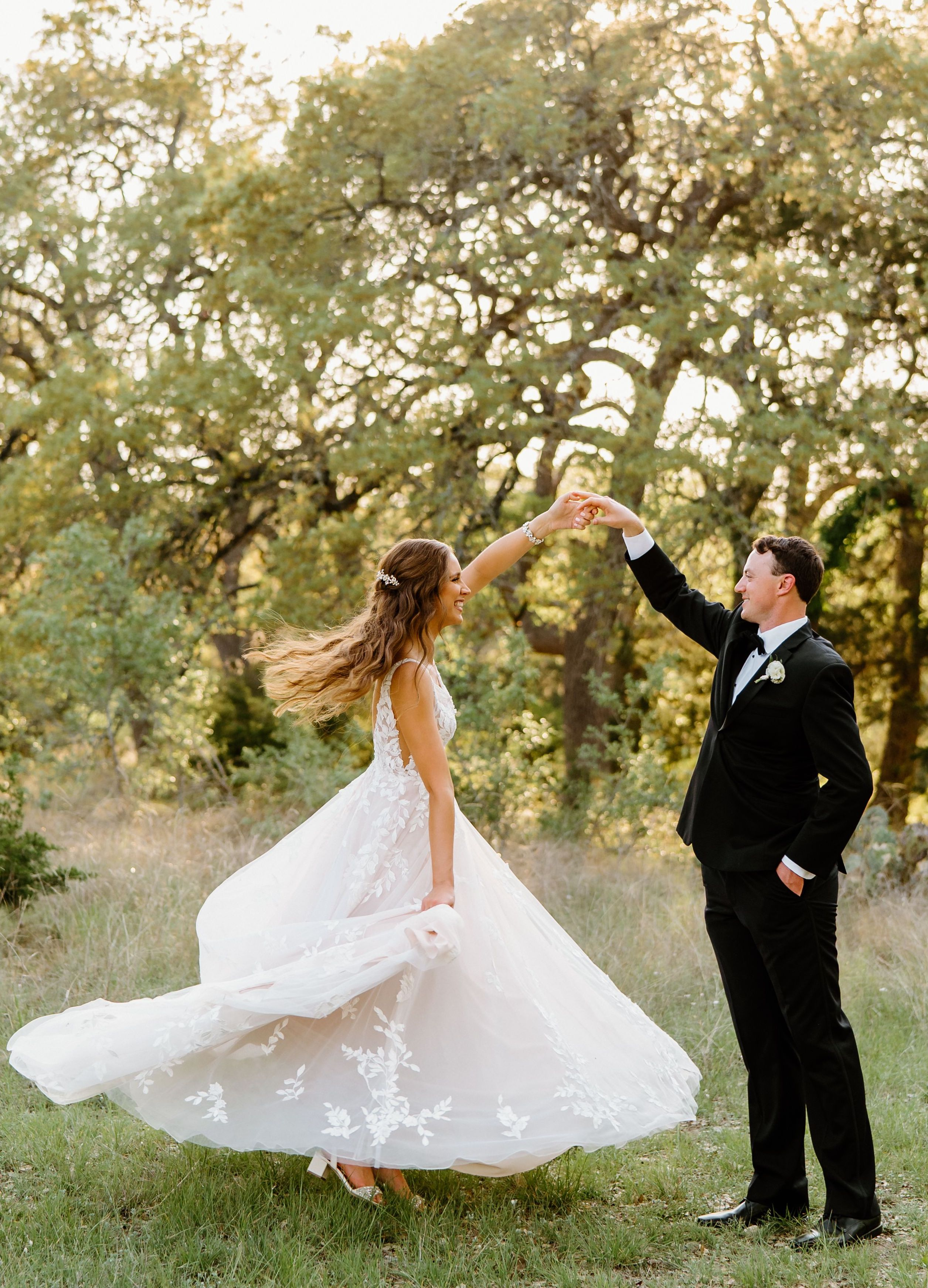 A groom twirls his new bride as her floral-adorned dress flares out revealing her sparkly block heels.