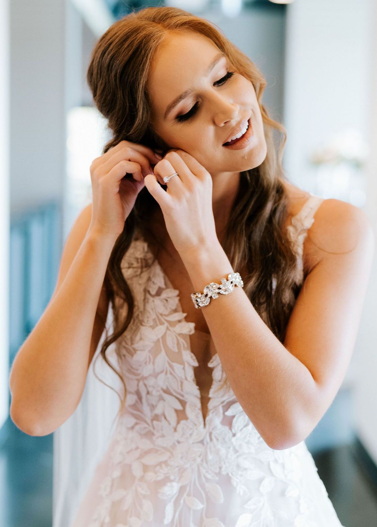 A bride in delicate, blush makeup and soft curls puts on her wedding earrings.