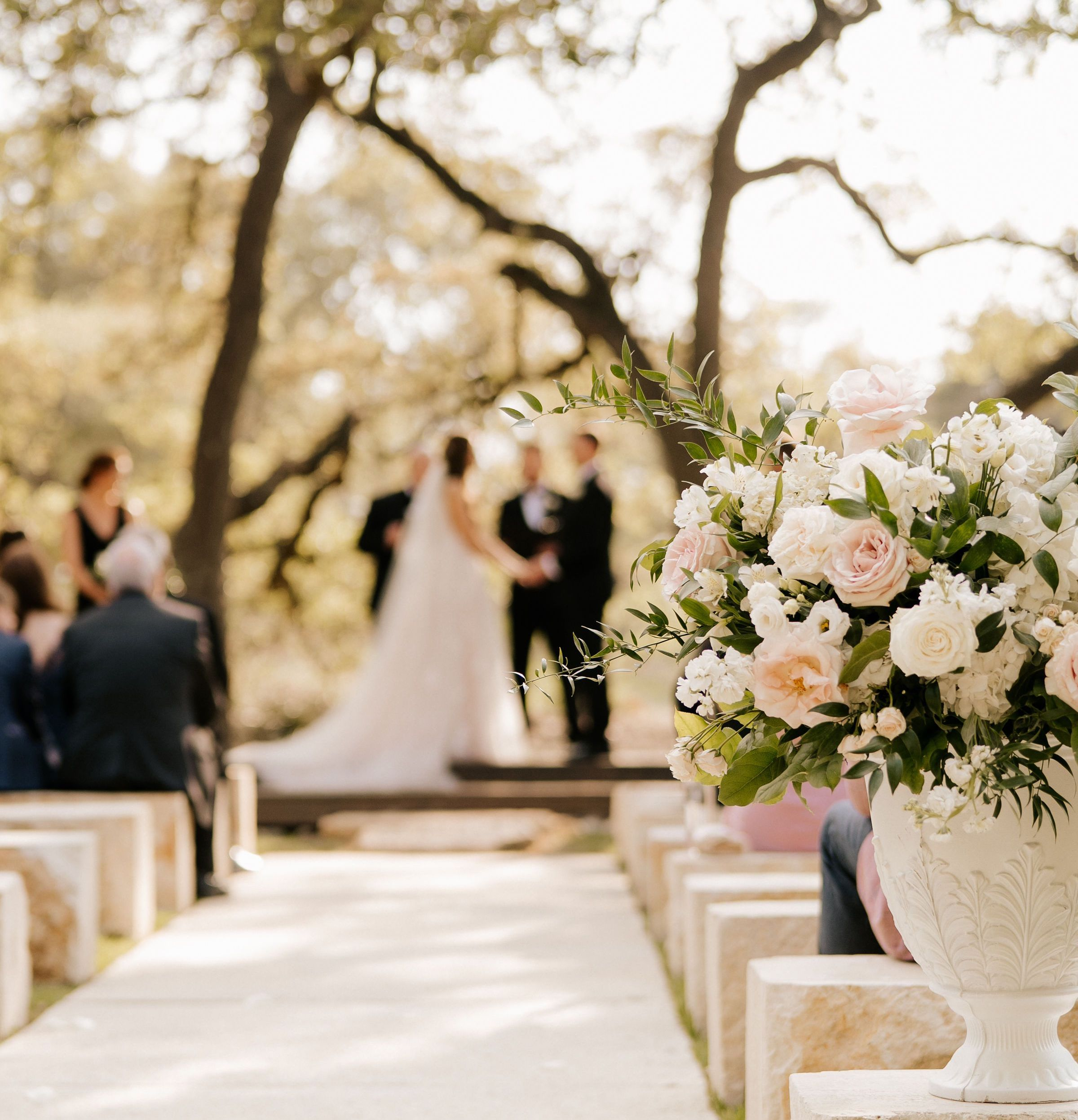 The couple stands under a canopy of trees in the distance while exchanging vows as a blush and white floral arrangement rests on a stone pew in focus.