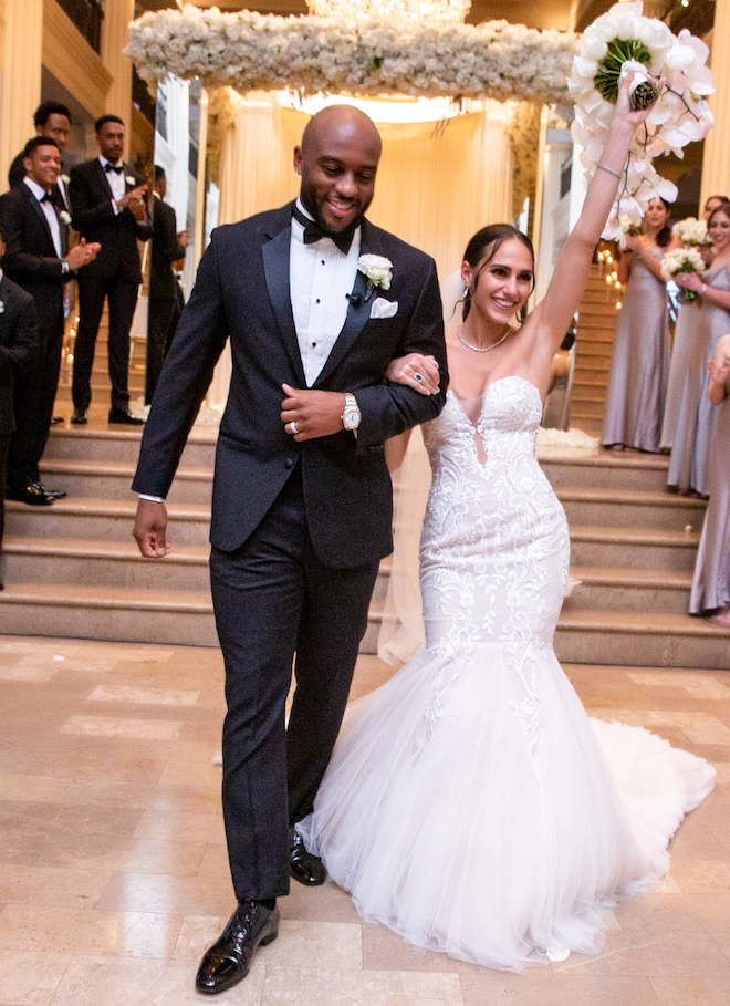 Bride lifts her bouquet up in one hand and she and her groom embrace and celebrate while they walk down the aisle.