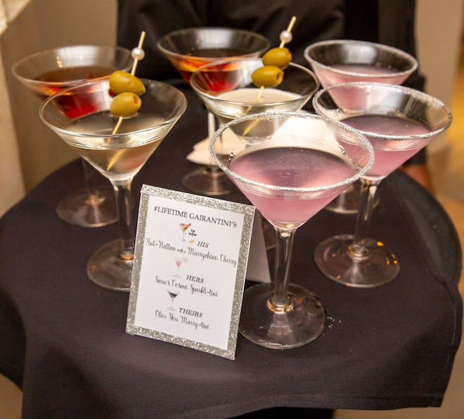 Eight custom light pink and red colored martinis with olives as garnishes.