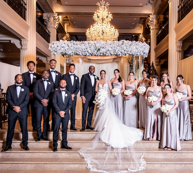 A photographical portrait of the bridesmaids, groomsmen, bride, and groom under a chandelier of the Corinthian Houston ballroom.