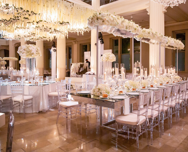 Reception set up and decor in white lush florals, hanging florals, and warm lighting.
