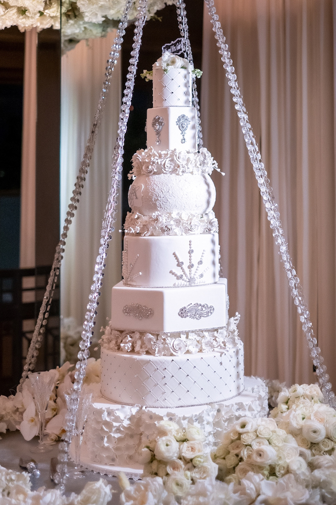 A white six tiered cake decorated in silver, crystal, and jewel like decorations and white roses.