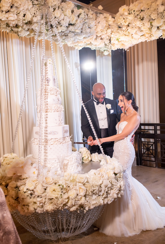 Bride and groom cut their six tiered cake, while the bride drops her jaw in excitement.