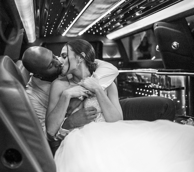 Groom and bride share a kiss as they embrace each other sitting inside of a limo.