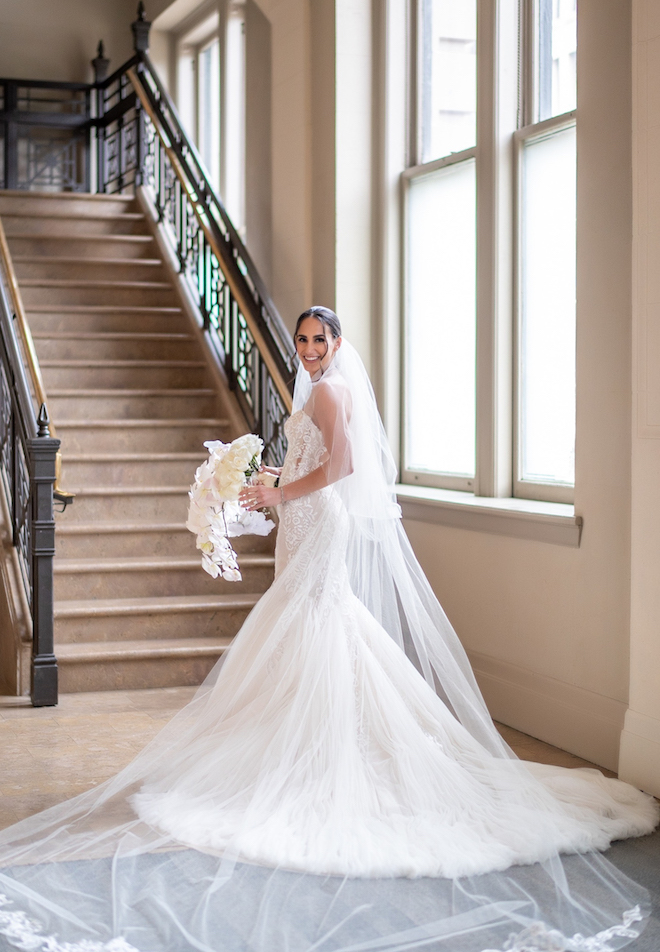 A bride is smiling as she holds her white floral bouquet and wears a long veil that extends across the floor.