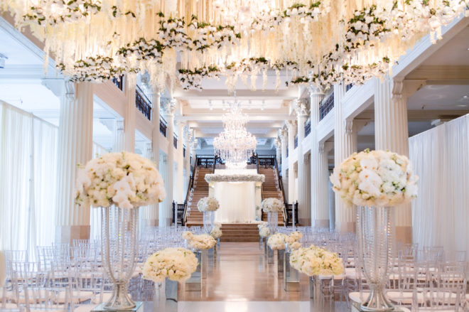 Ballroom of The Corinthian Houston decorated with many white florals hanging from the ceiling and down the aisle in floral arrangements.