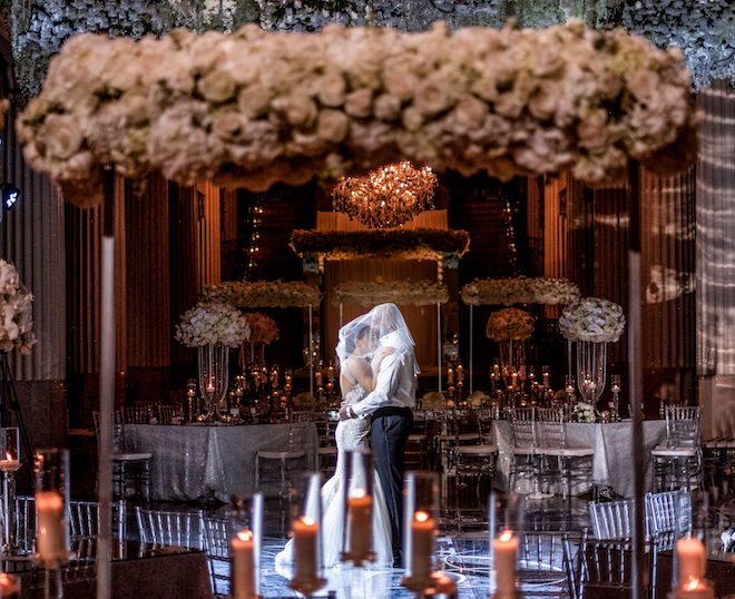 Bride dances with a groom with her long veil over both their heads in a dimly lit Grand Hall decorated with candlelights, white roses and tall centerpieces at the downtown Houston wedding venue, Corinthian Houston.