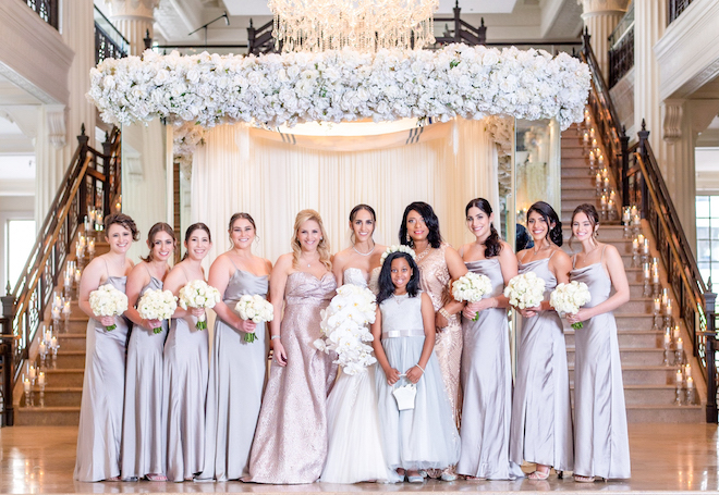 Bride and bridesmaids under a canopy of white lush florals in front of a grand staircase at The Corinthian Houston.