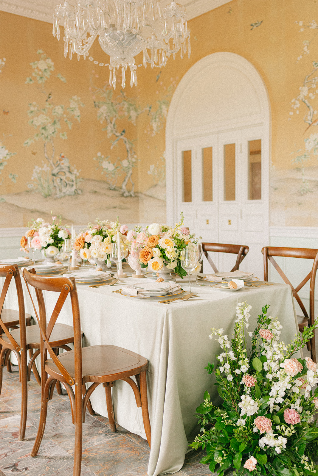 Reception room at The Mansion at ColoVista for the artfully curated styled shoot. Flowers are covering the table and there is a crystal chandelier hanging above the dining table.