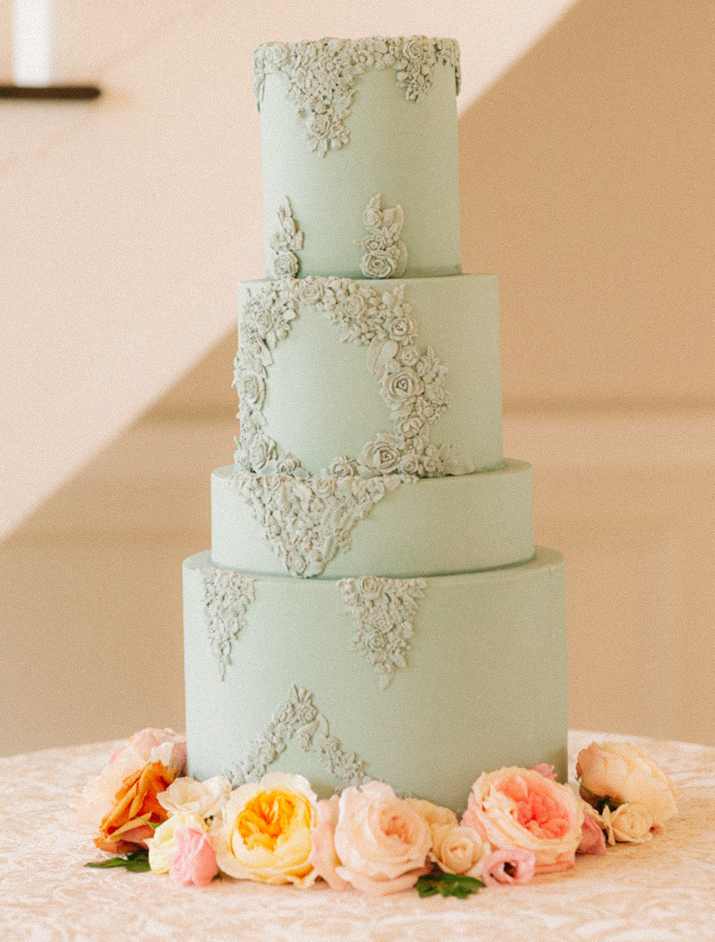 4-tiered wedding cake with sage green frosting with artfully curated flowers at the base.