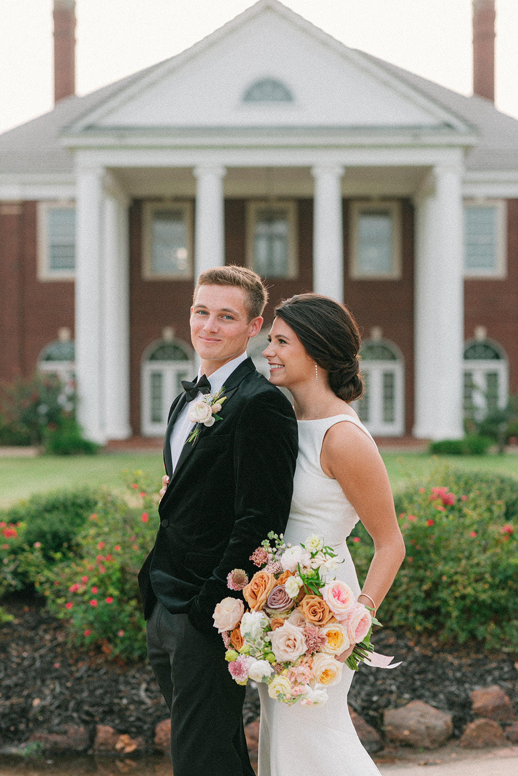 Bride smiles up at the groom while holding her artfully designed bridal bouquet. The couple is standing in front of the Mansion at ColoVista.