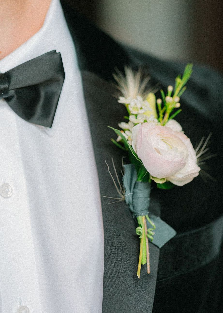 Groom wears an artfully designed boutonnière for the southern styled shoot.