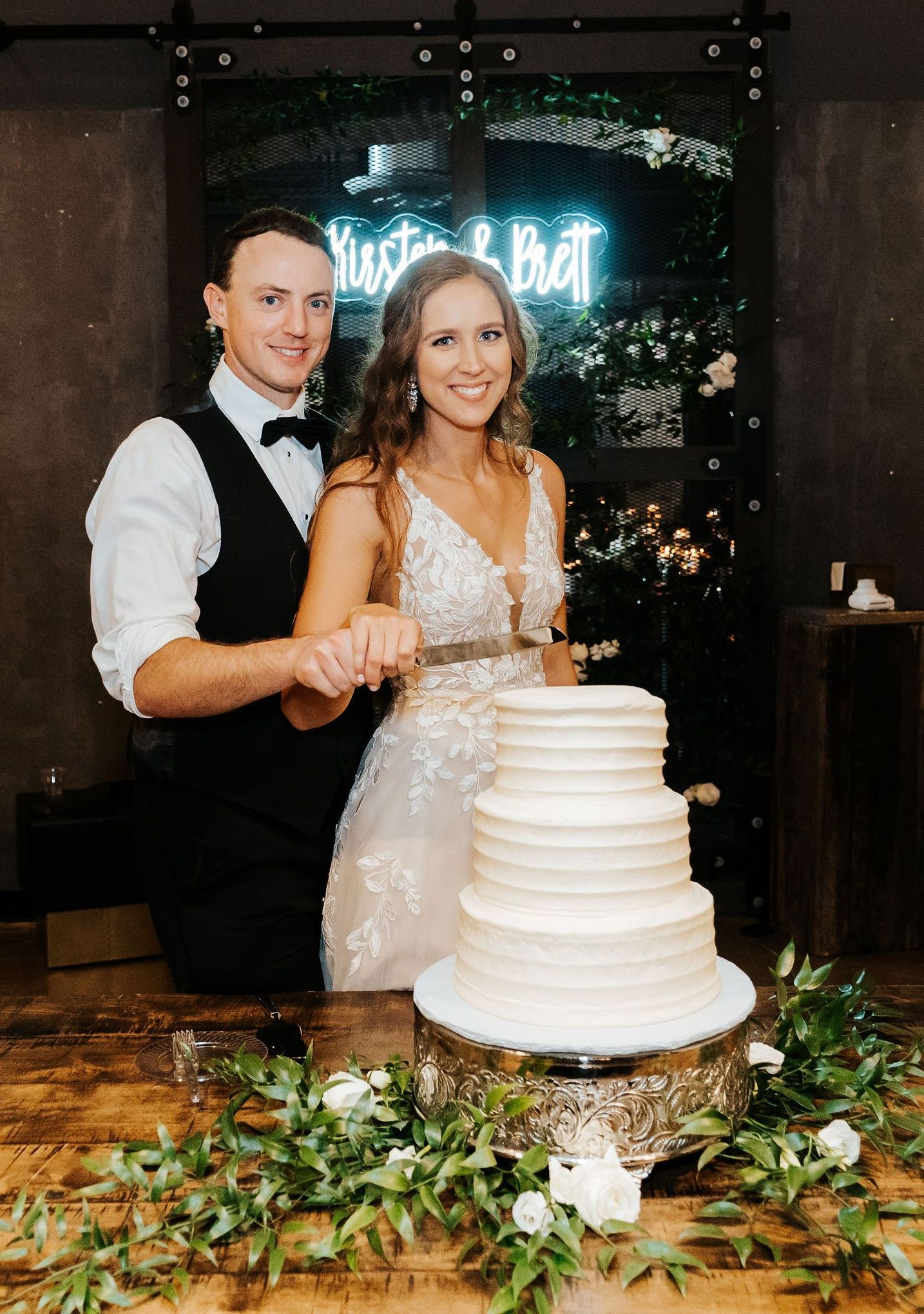 Kirsten and Brett prepare to cut their three-tiered plain white cake while a neon sign with the couple's names shines bright in the background.