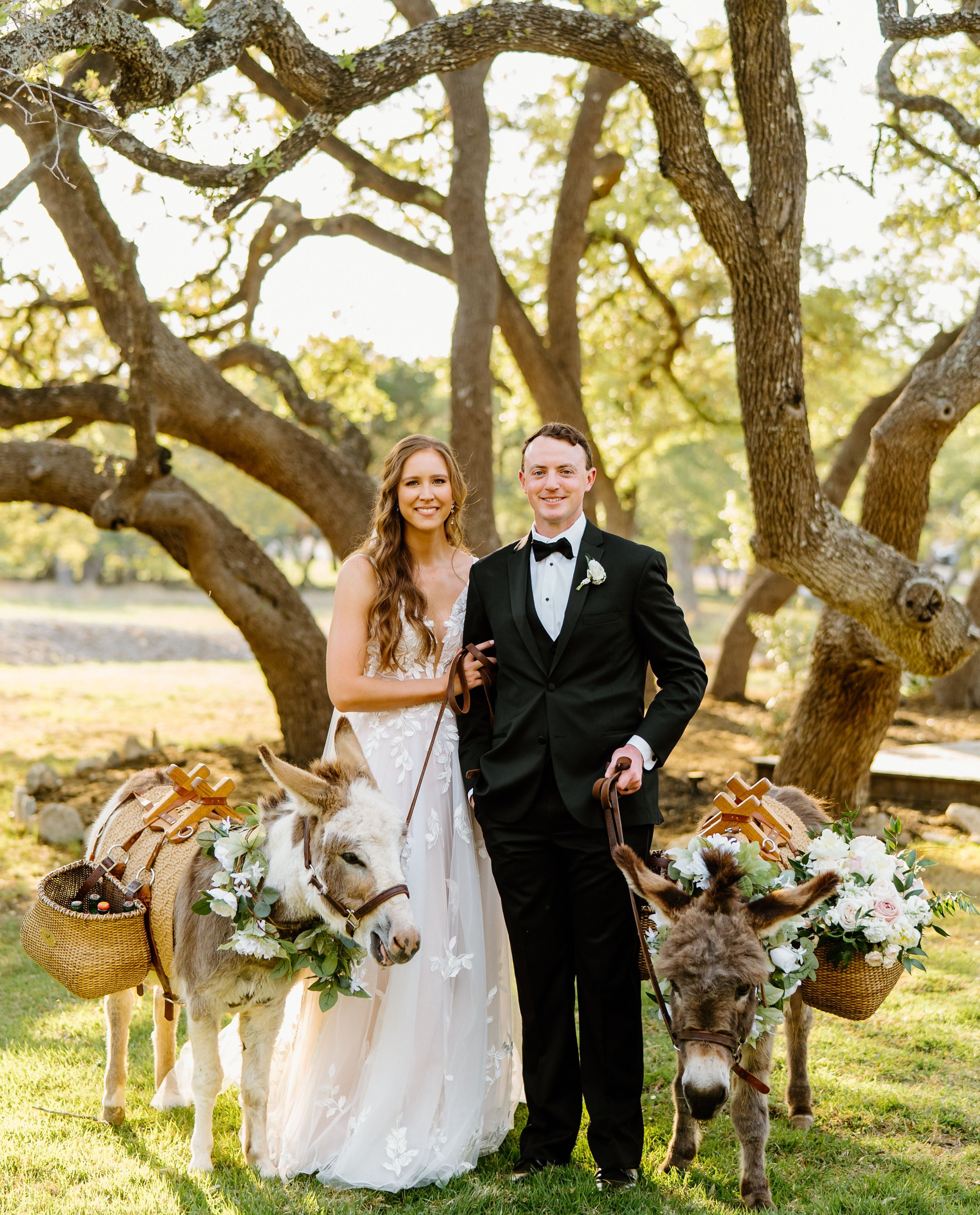 A smiling bride and groom are flanked by two floral adorned beer burros with a towering oak tree behind them.