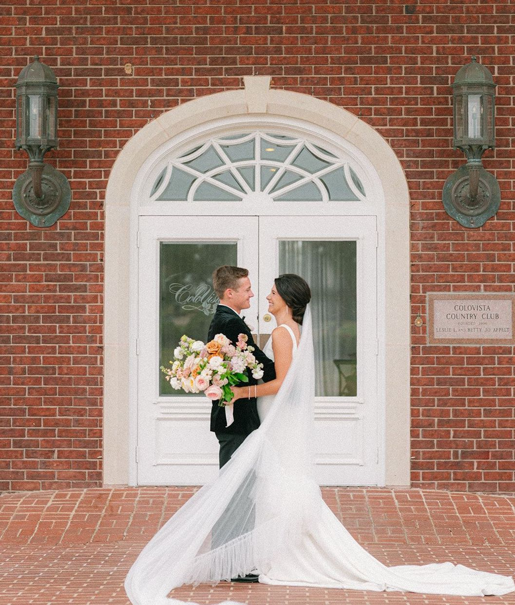 Bride and groom smile at each in front of The Mansion at ColoVista for the southern styled shoot.