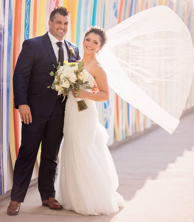 Groom and bride, with veil blowing in wind, pose in front of colorful outdoor surf boards at their lakeside wedding at Margaritaville Lake Resort, Lake Conroe and Houston.