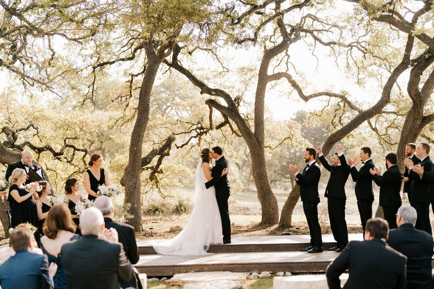 A newlywed couple exchanges a kiss under a natural arch of trees in Texas hill country.