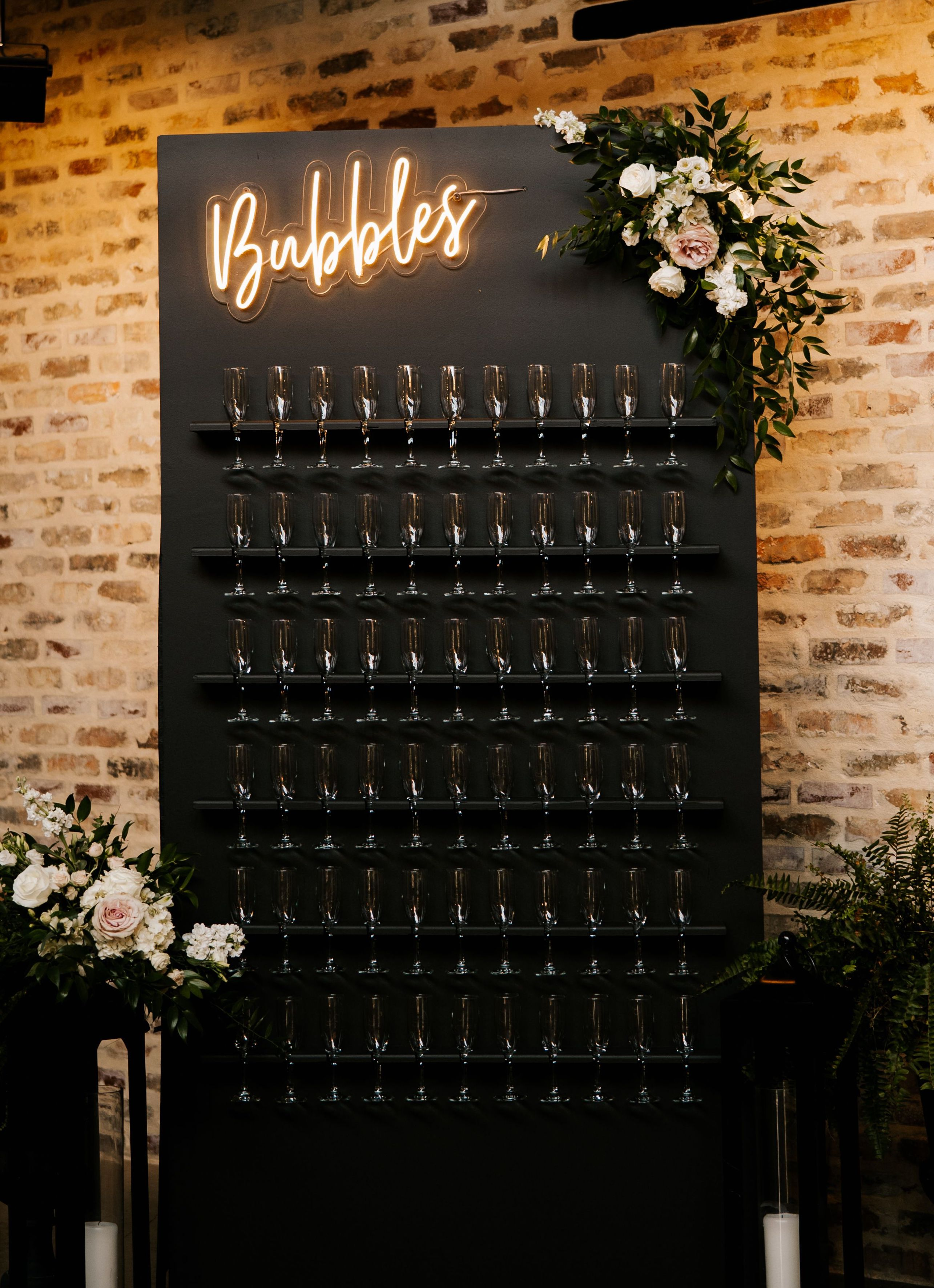 A black champagne wall installment is adorned with white and blush floral arrangements standing in front of a distressed brick wall.