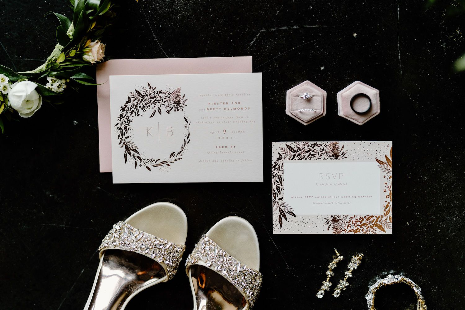 A flat lay showcases a couple's black, white, and blush floral wedding invitations, the bride's jewelry, and her dazzling wedding shoes.