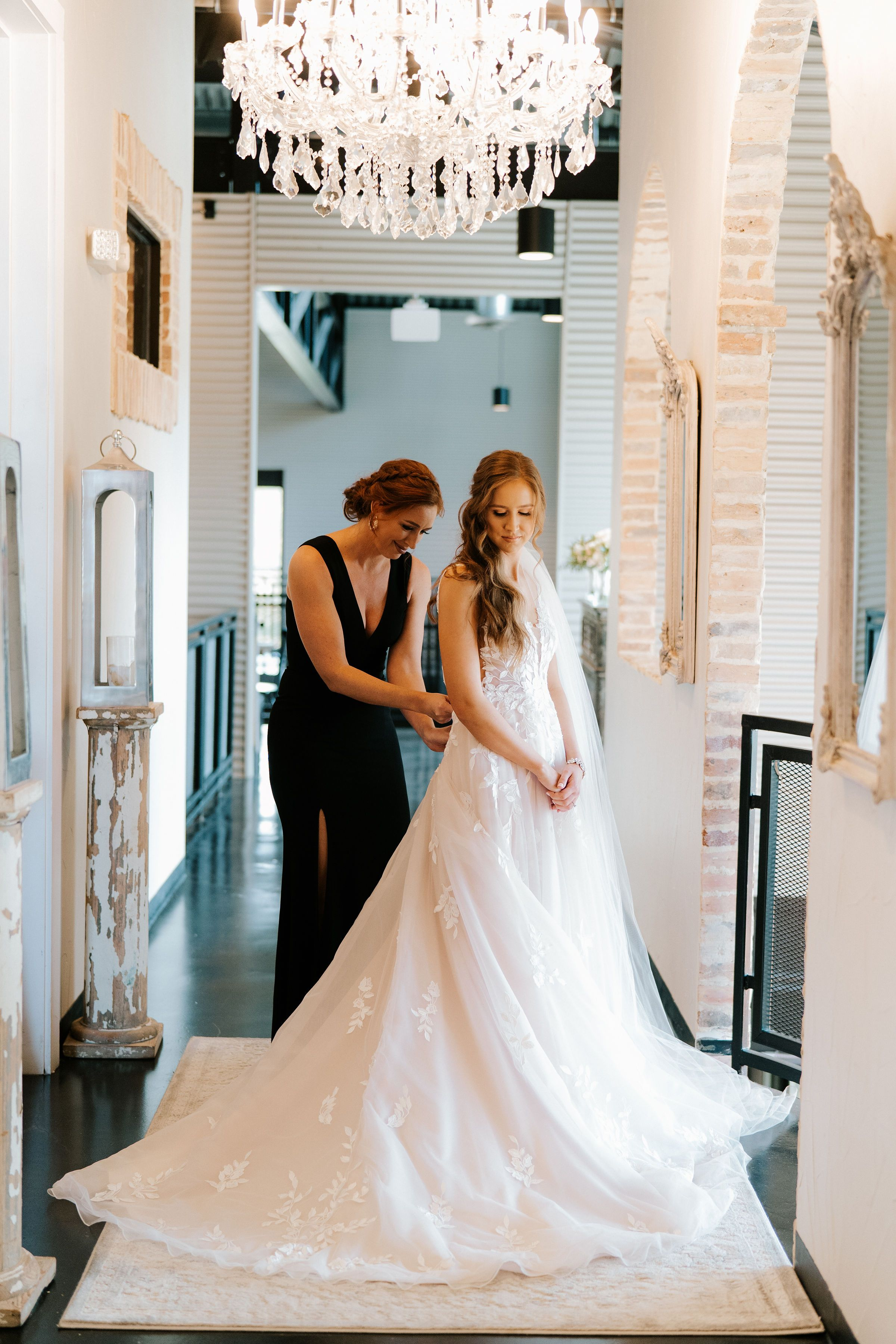 A bridesmaid finishes buttoning her friend's Essence of Australia wedding dress before her industrial chic wedding.