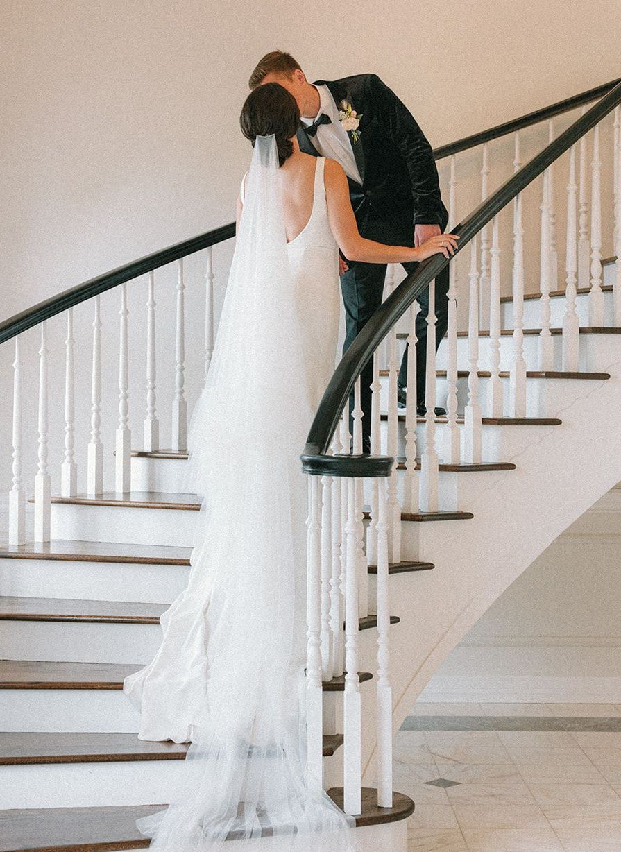 Bride and groom kiss on the grand stairwell at The Mansion at ColoVista for their southern styled shoot.