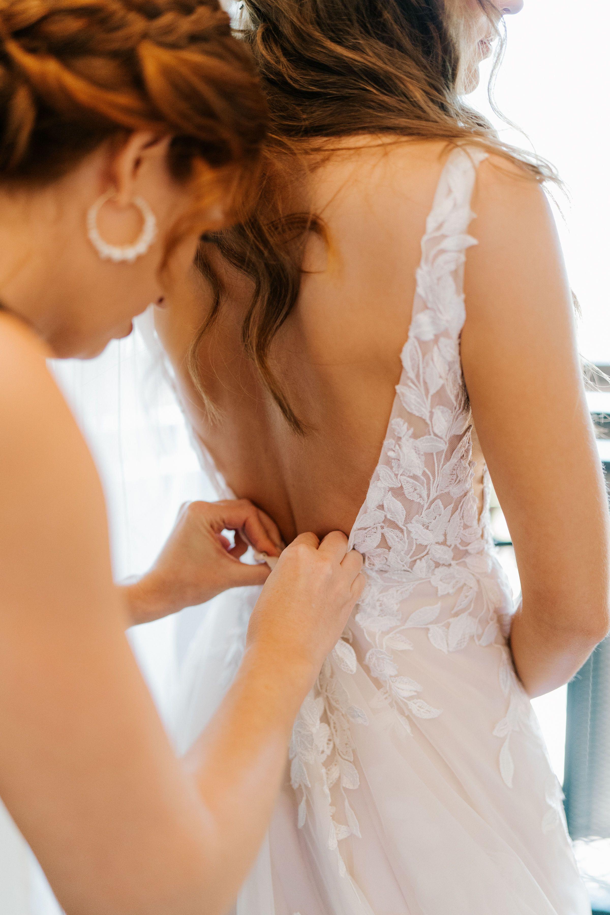 A friend helps a bride into her Essense of Australia wedding dress adorned with leafy appliques.