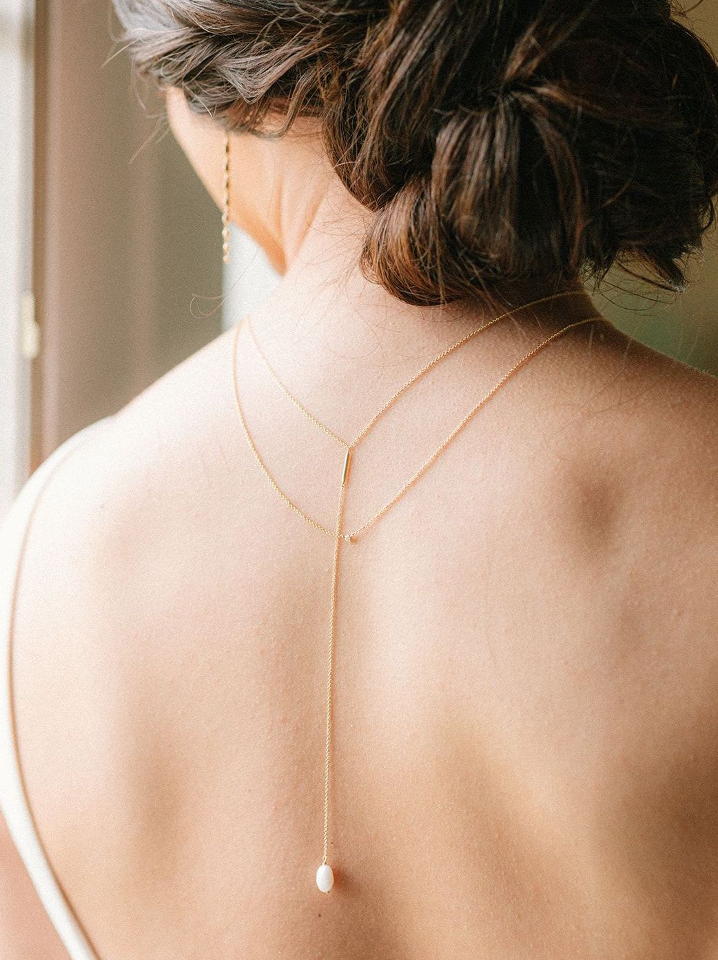 Bride's back is turned to show the pearl backing of her artfully designed necklace for the styled shoot.
