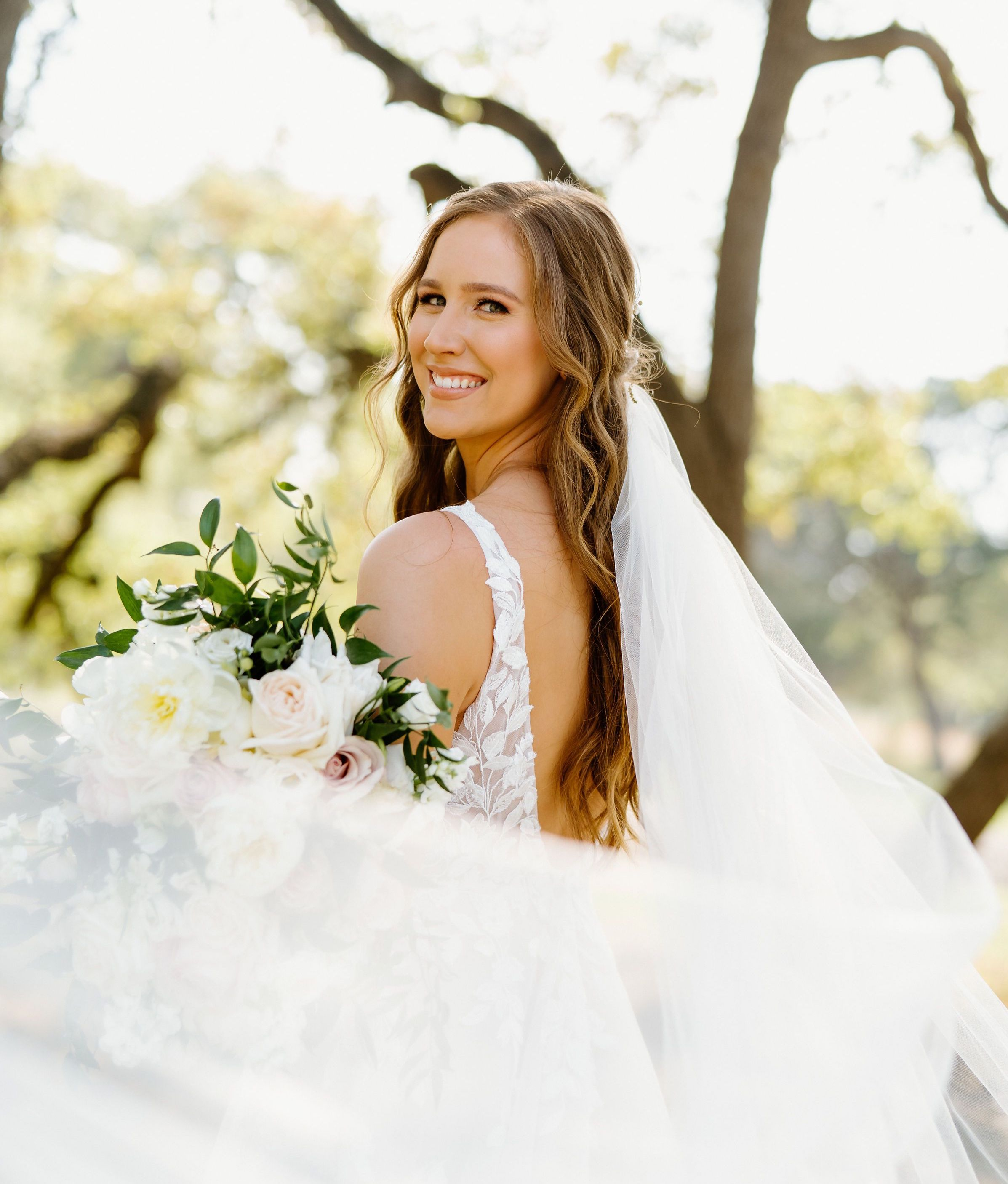 A beautiful bride is all smiles holding her bouquet as her cathedral length veil swirls out from behind her, catching the wind in a Texas Hill Country wedding designed by Scarlet Rose Events.