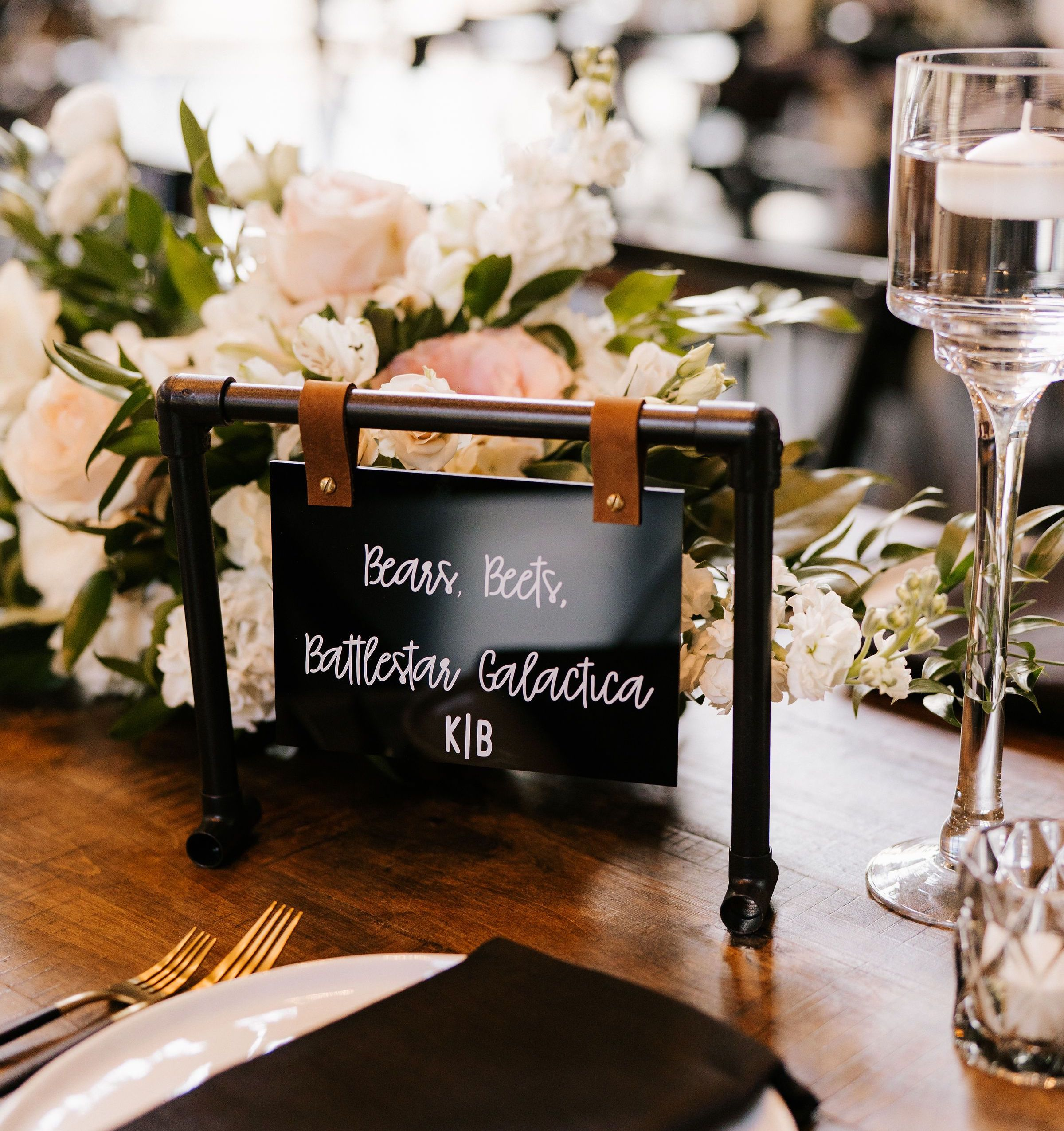 Custom industrial chic wedding table cards made of faux-iron pipe, acrylic, and leather straps display the couple's creative table names.