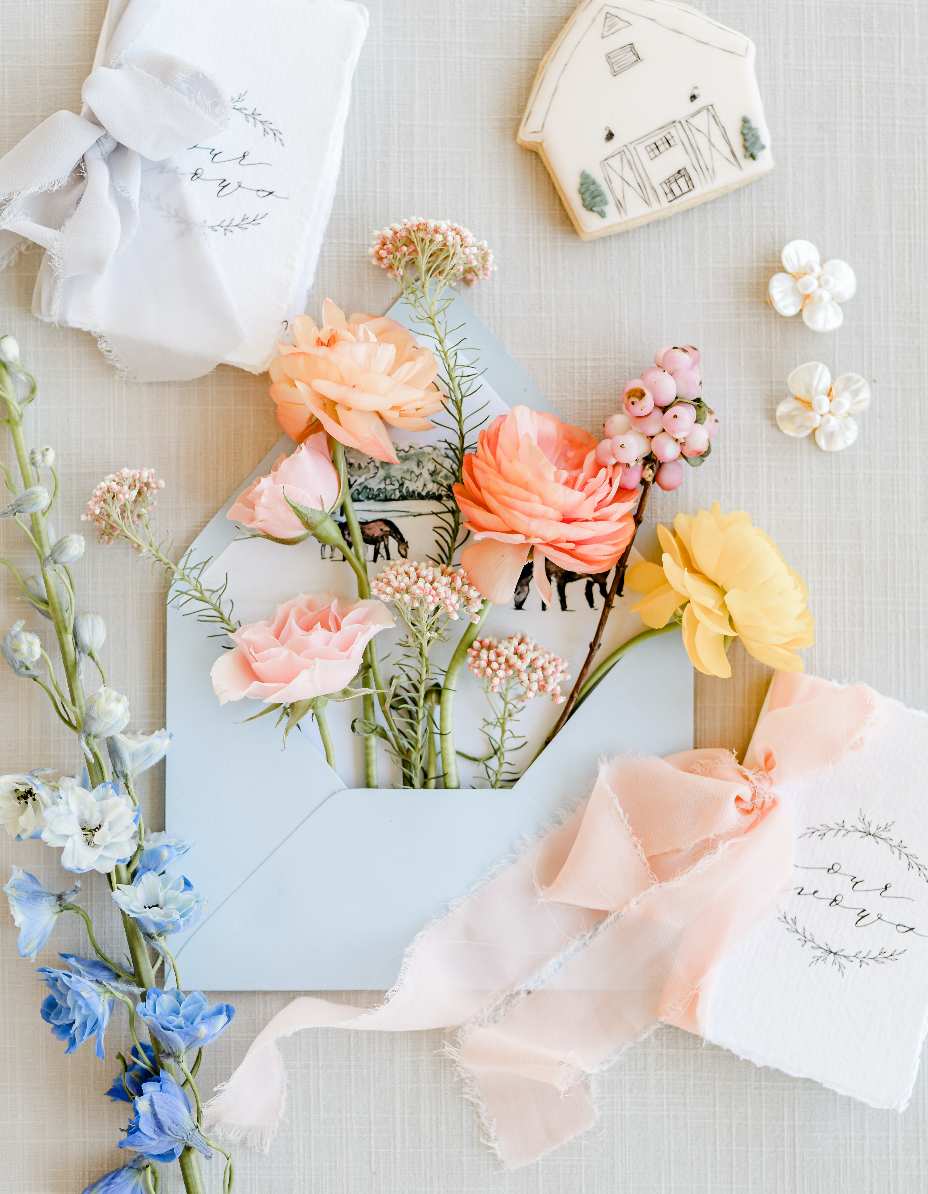 Colorful flowers flow out of a blue envelope for Crystal and Micheal's friendly spring wedding.