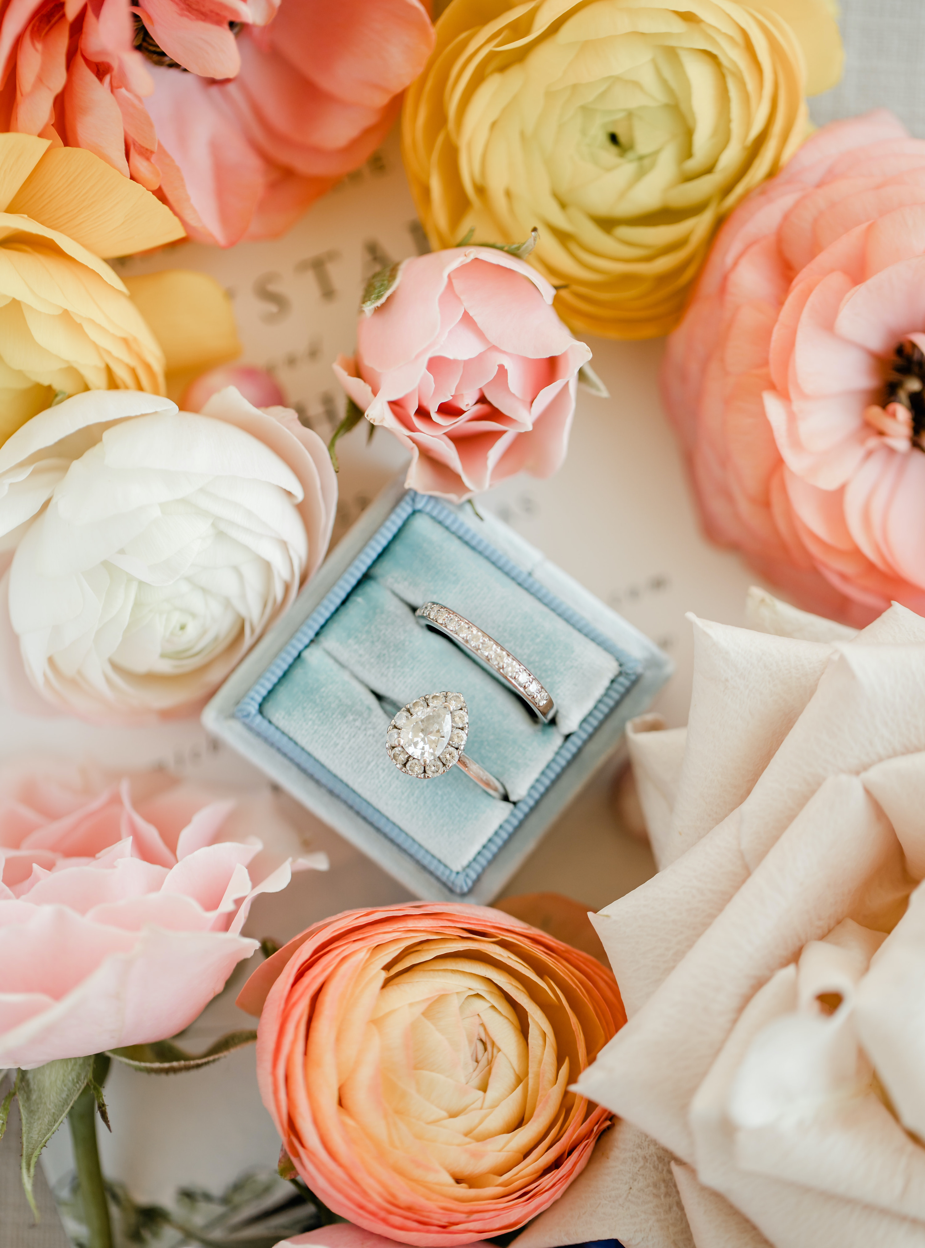 An engagement ring in a blue box surrounded by vibrant flowers.
