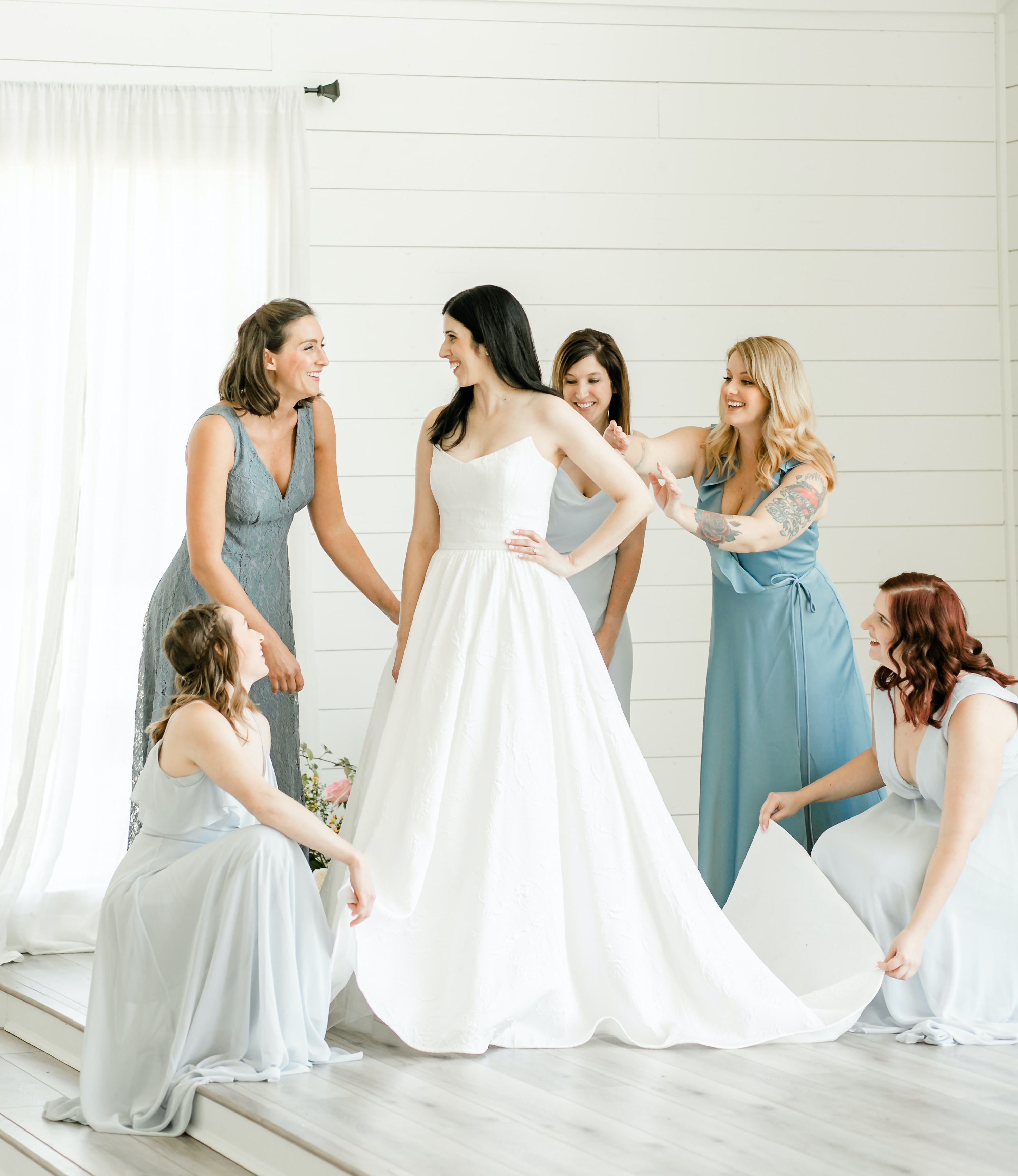 The bride gets ready with her bridesmaids, who are in different shades of blue dresses.