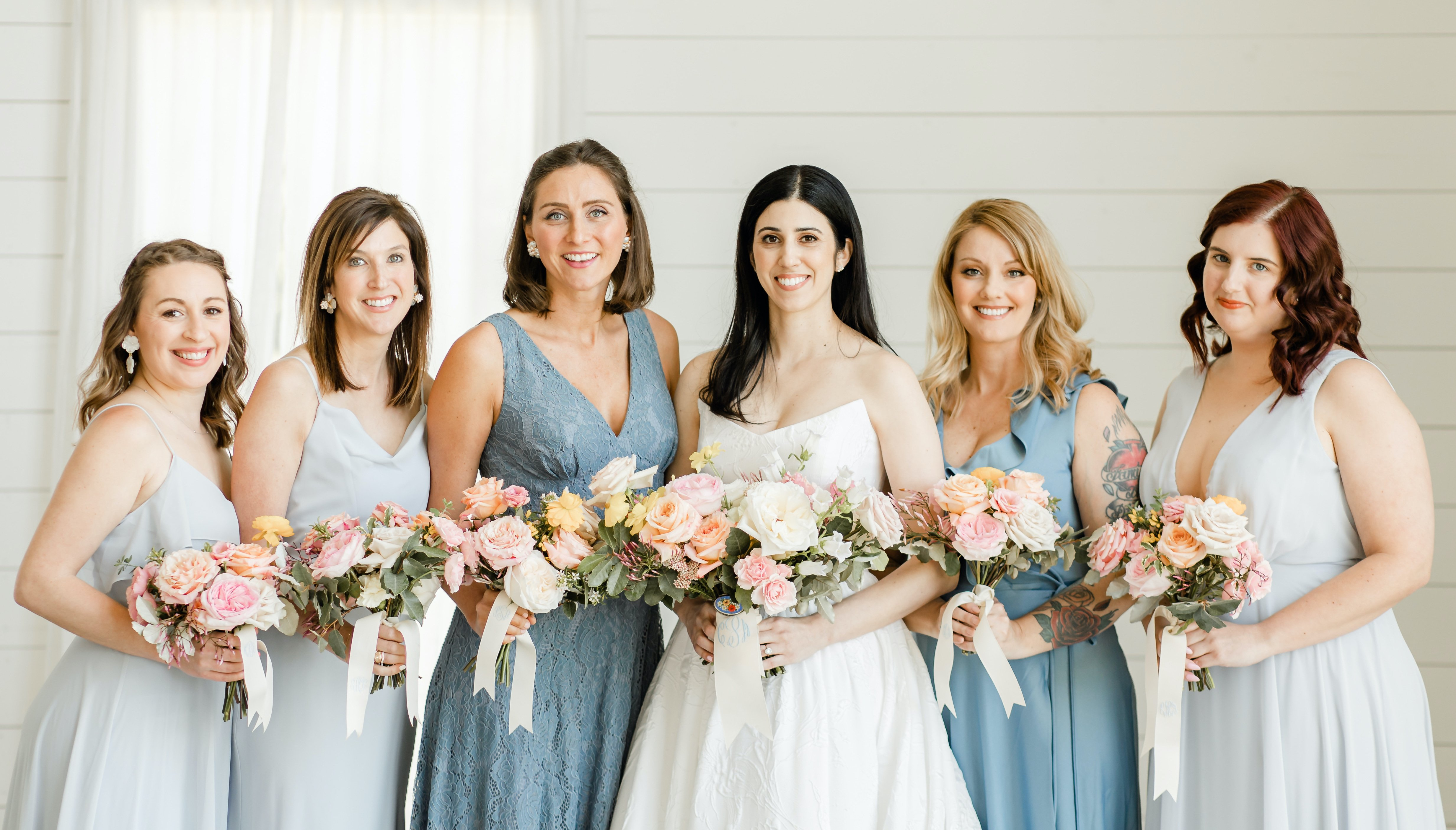 The bride smiles with her bridesmaids and they all hold their colorful bouquets.