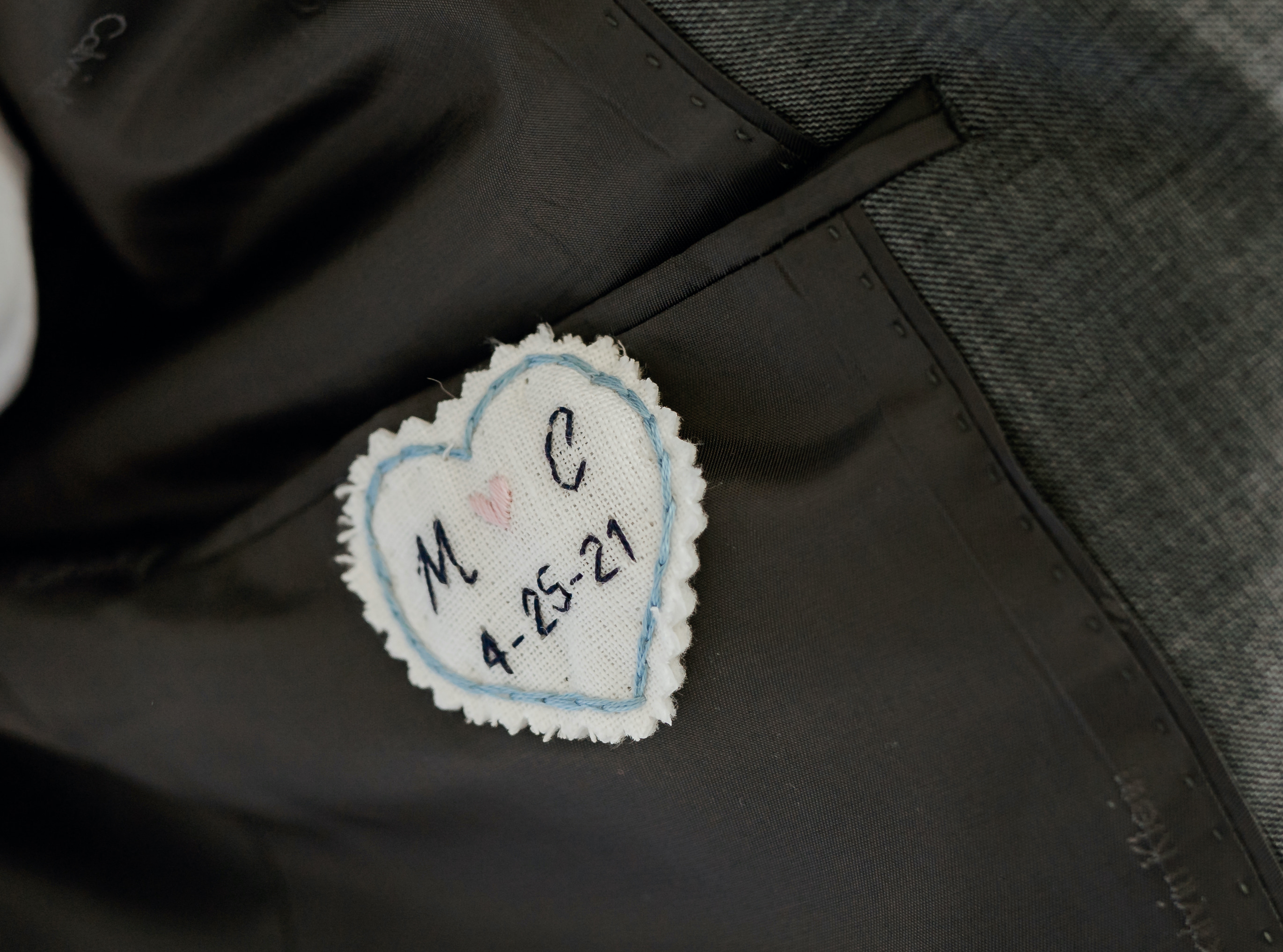 An embroidered heart inside the groom's suitcoat.