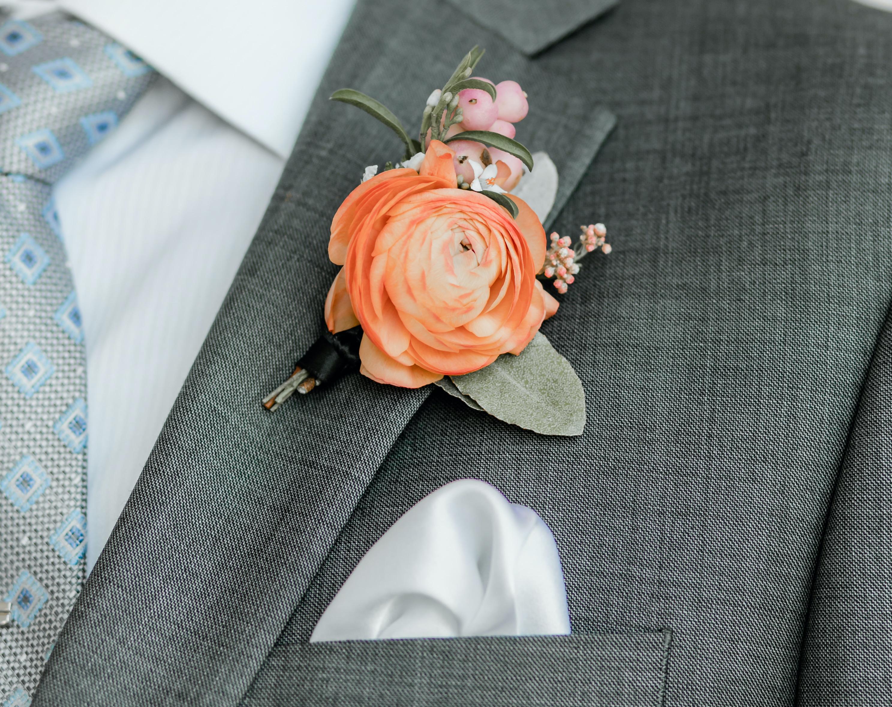 The groom's vibrant orange boutonierre.