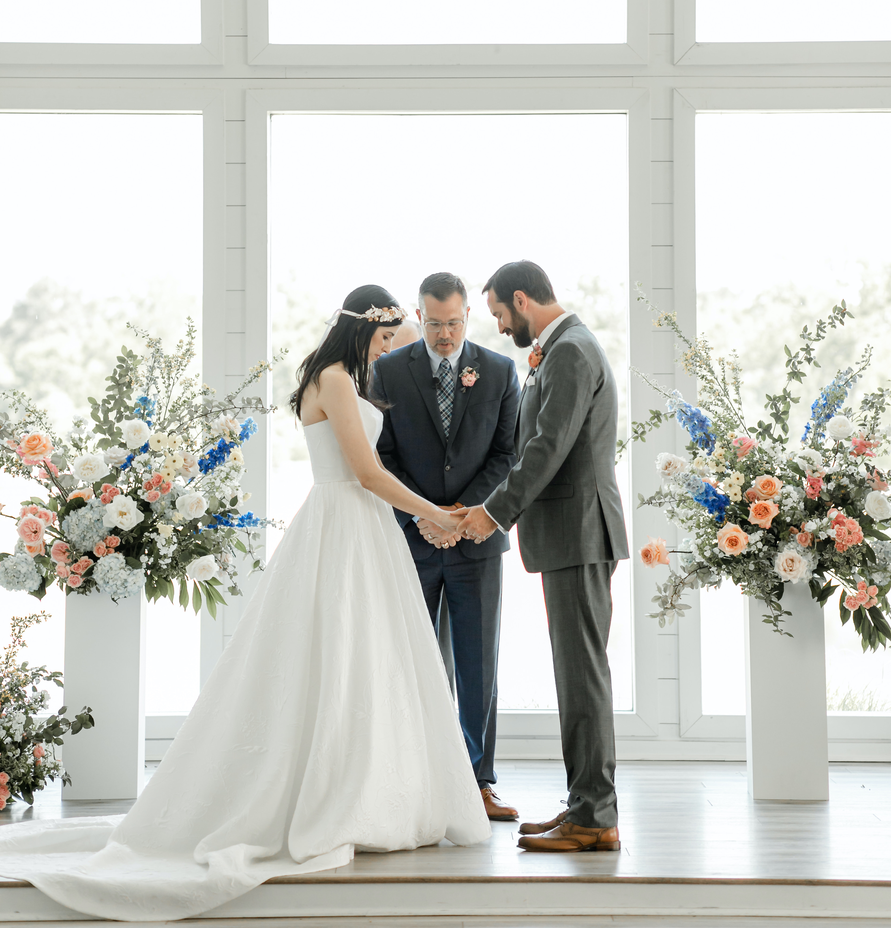 The bride and groom stand at the altar holding hands with flowers surrounding them.