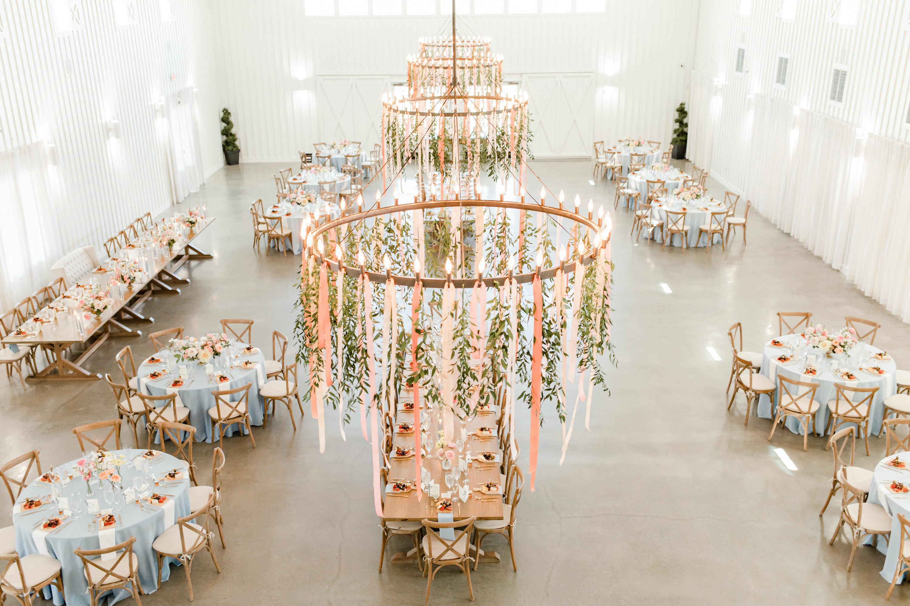 The chandeliers in the reception room have colorful streamers hanging from them with sunshine pouring into the room.