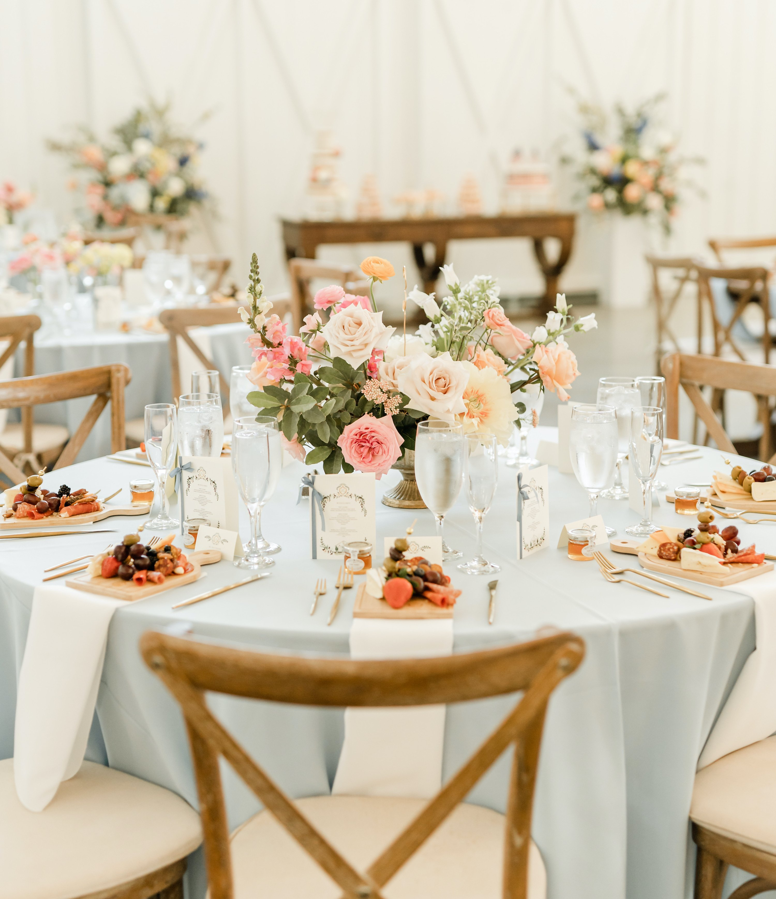 The reception tables are set with a light blue table cloth and a charcuterie board is placed at each guests seat, who are close friends of the bride and groom.