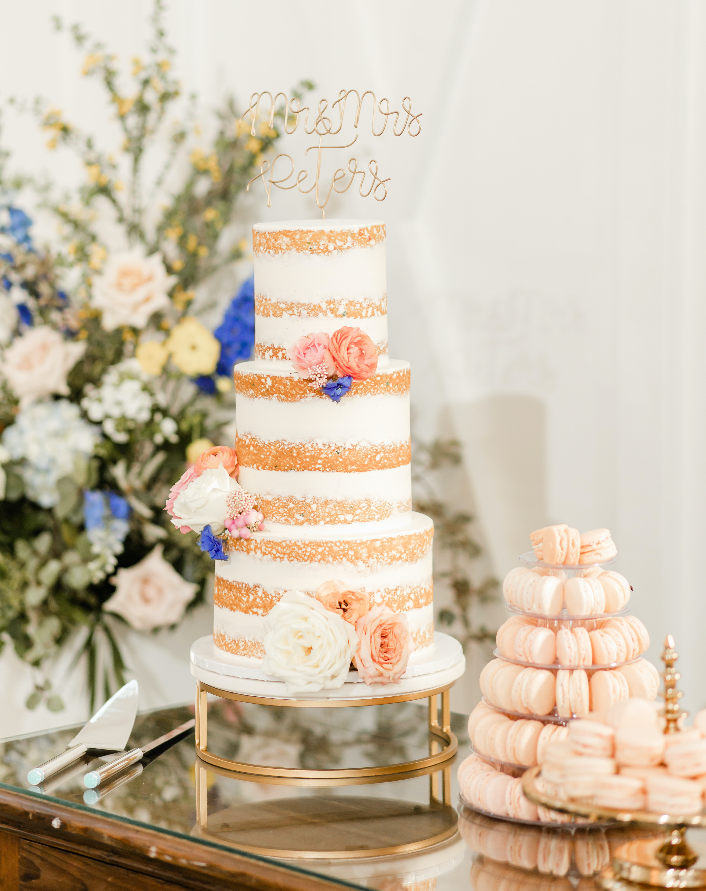 A beautiful cake with white frosting and peach macarons next to it.