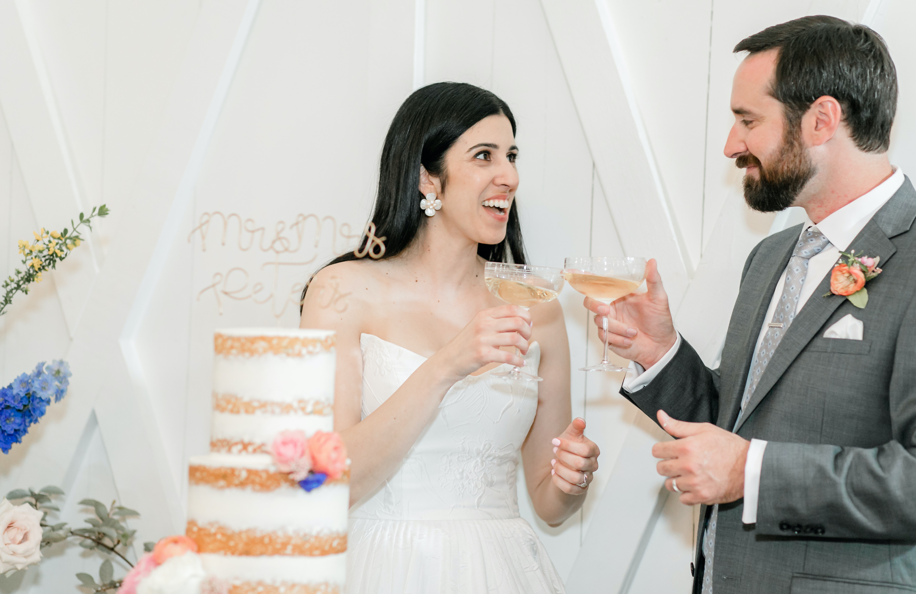 The bride smiles at the groom as they cheers glasses by their wedding cake.