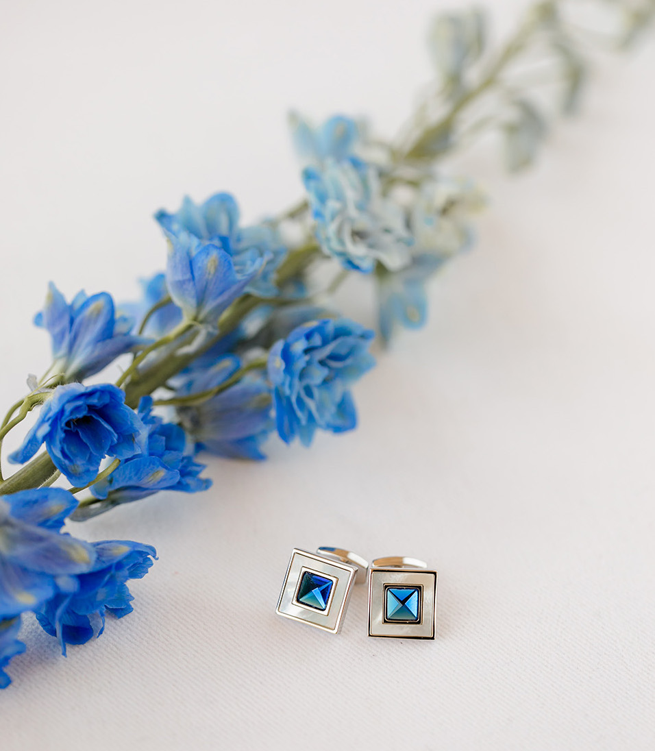 The groom's cuff links have a vibrant blue gem and sit next to a piece of Delphinium.