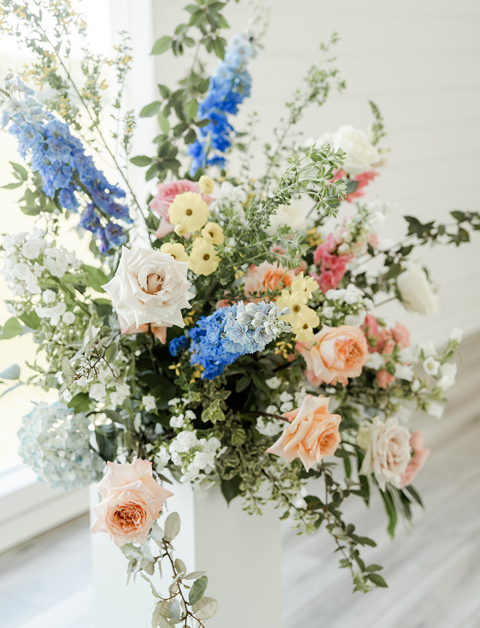 Vibrant flowers in blue, yellow and peach are designed in an arrangement on the altar.