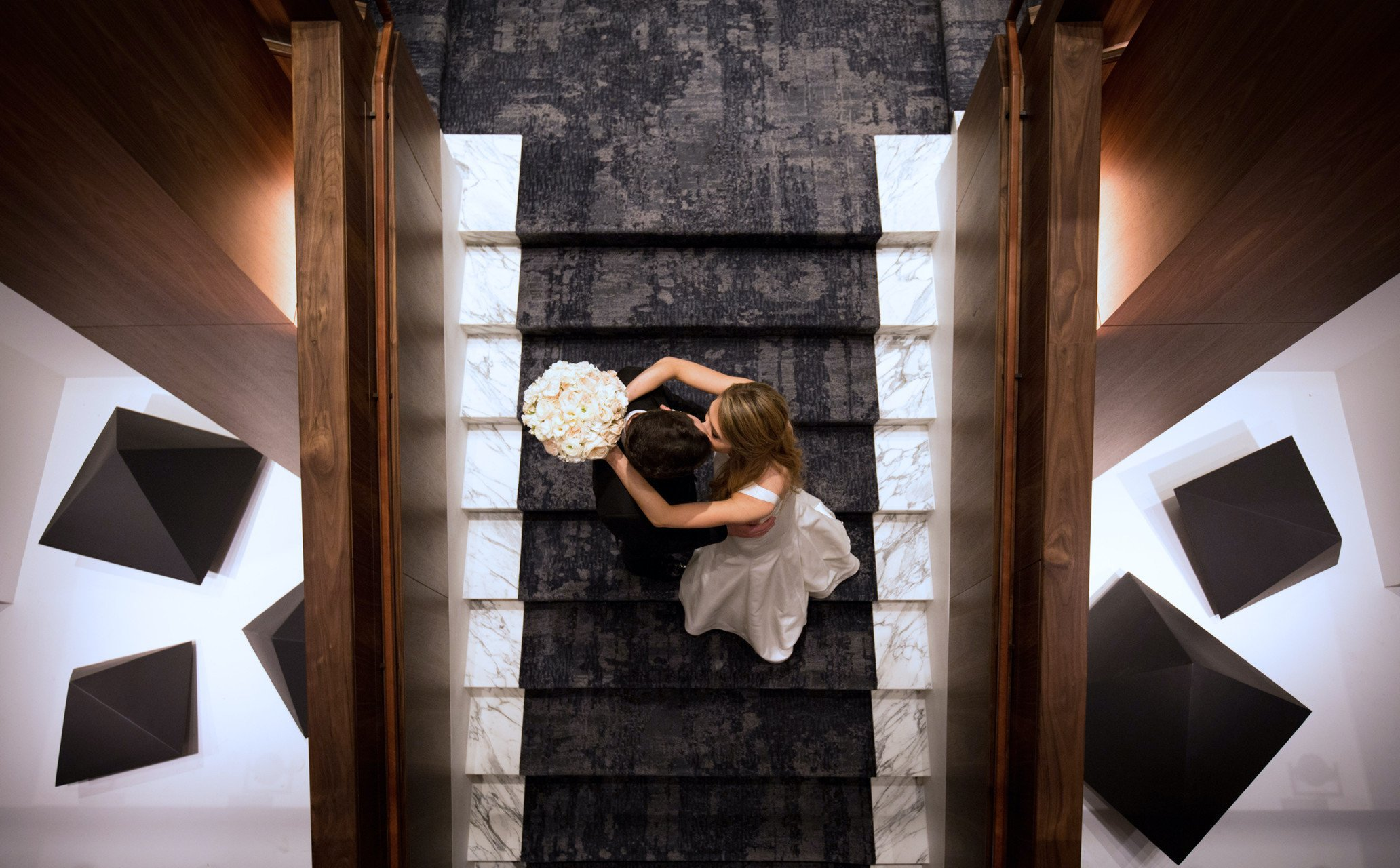 The bouquet holding bride and suited groom kiss each other on the Four Seasons Hotel Houston stairs.