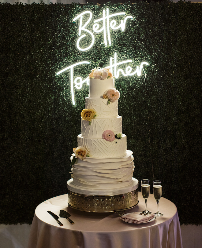 """The wedding cake with a neon sign behind it that says """" Better Together."""""""