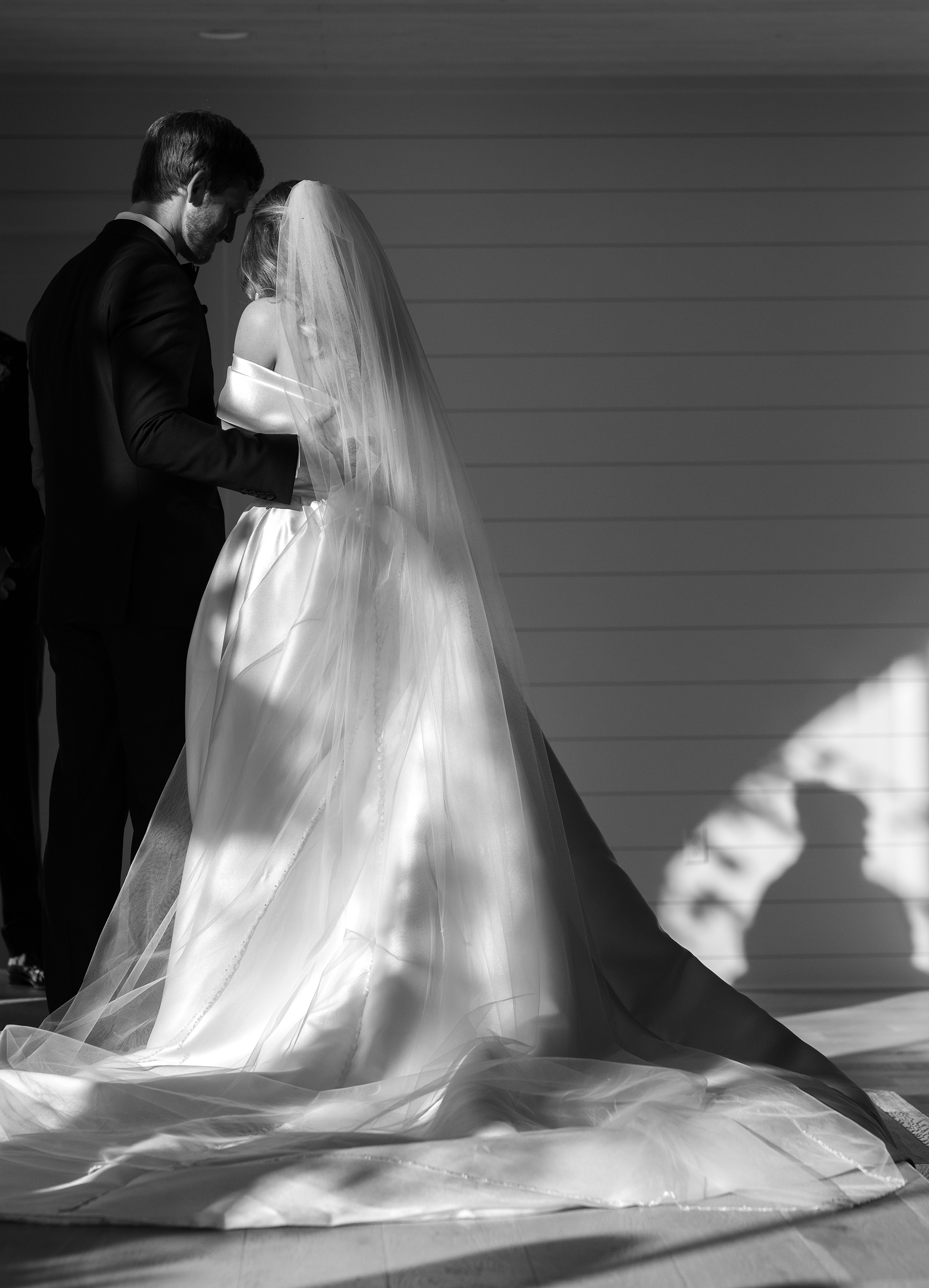 A black and white photo of the bride and groom's back with the sunlight shining onto them.