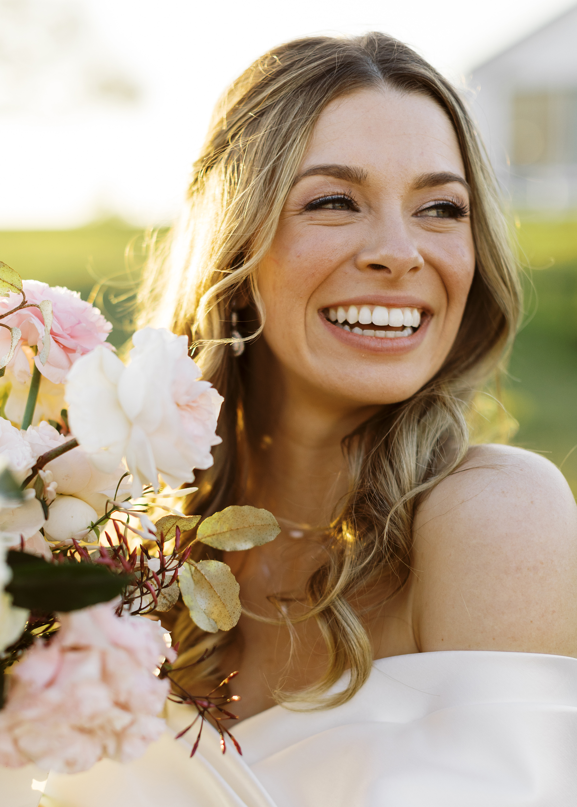 The bride is smiling while holding her bridal bouquet.