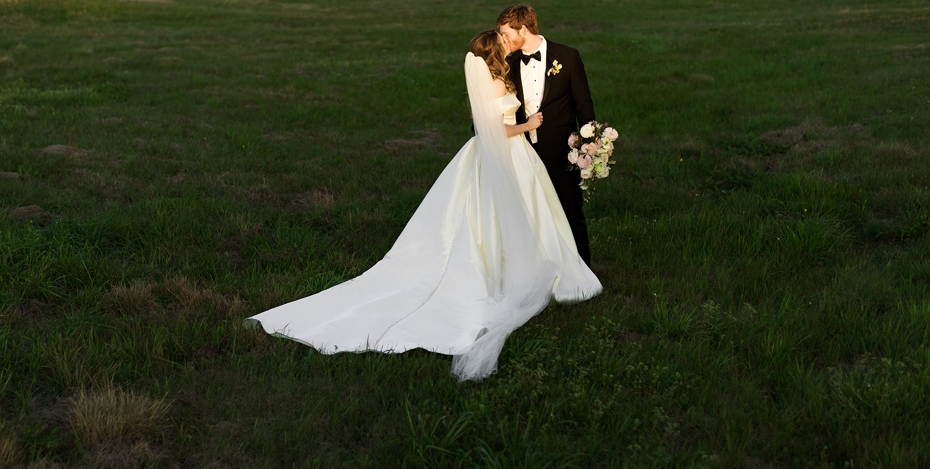 The bride and groom embrace each other in a green open field.