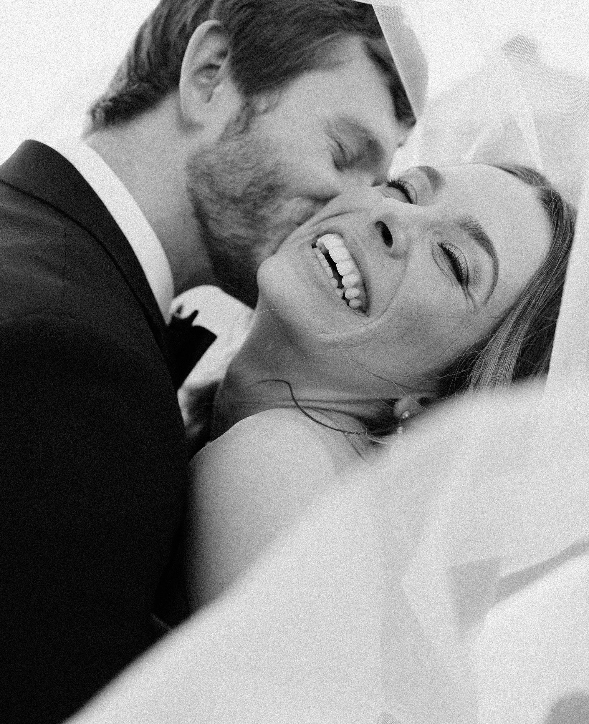 The groom kisses the brides cheek as she laughs at their wedding at venue Deep In The Heart Farms in Brenham, Texas